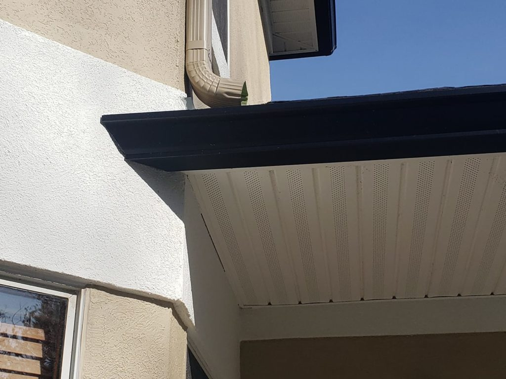 "Disappearing 6"" gutter into angled stucco wall."